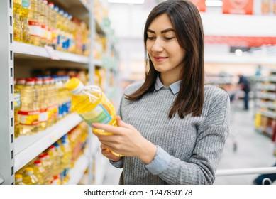 Woman choosing sunflower oil in a supermarket