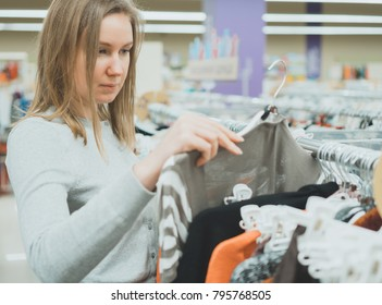 Woman choosing sweater in clothing store.