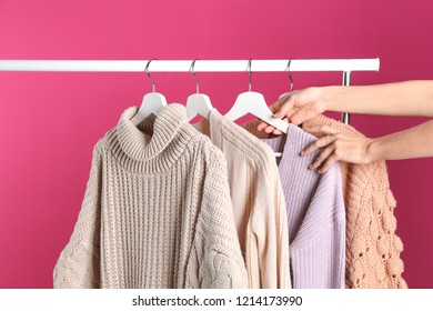 Woman choosing sweater on rack against color background
