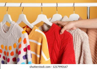 Woman choosing sweater on rack against color background, closeup