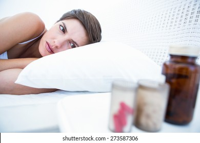 Woman choosing to take pills or not at home in the bedroom