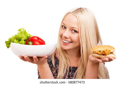 woman choosing what to eat, vegetables or burger, isolated against white background