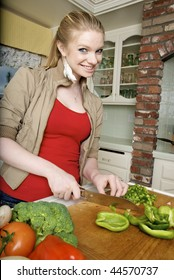Woman Chopping up a Green Pepper in the kitchen
