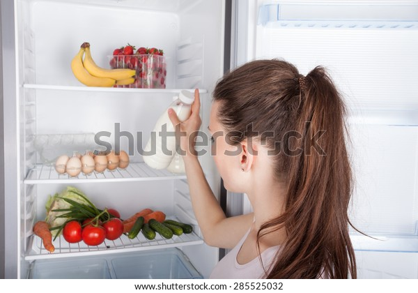 Woman chosen milk in opened refrigerator,  healthy eating concept