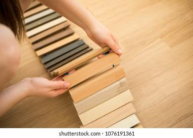 Woman chosing right flooring for her new apartment, floor sampler