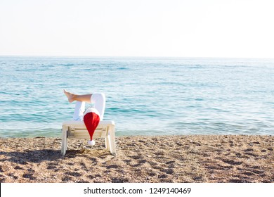 Woman in Christmas cap and white trousers lying on the beach chaise. Santa Claus on vacation. Christmas holiday. Winter resort. Christmas in Australia.