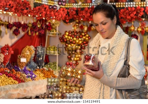 Woman at christmas decoration shop holding boxes of Xmas balls