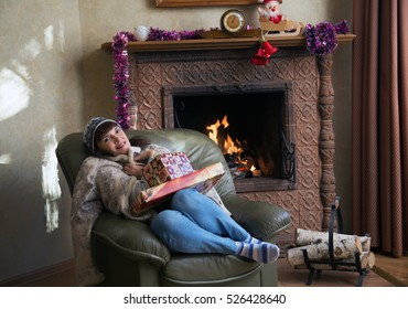 Woman with Christmas gifts by the fireplace