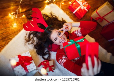 Woman with christmas lights and presents lying on floor and taking selfie