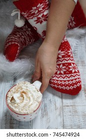 Woman in Christmas socks and hot chocolate drink. Person relaxing at home. Winter holiday Xmas and New Year concept