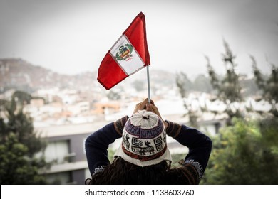 woman with chullo in the head is holding peru flag raising both hands on park background
