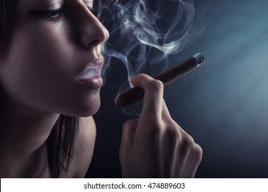 Woman with cigar exhaling smoke on a dark background
