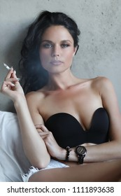 Woman with cigarette in a bed