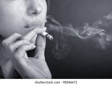 Woman with Cigarette Exhaling SmokeWoman with Cigarette Exhaling Smoke. Black and white photo