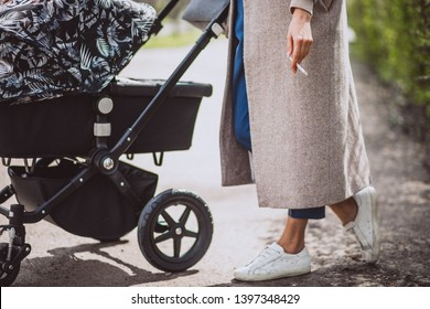 Woman with cigarette smoking by the baby carriage