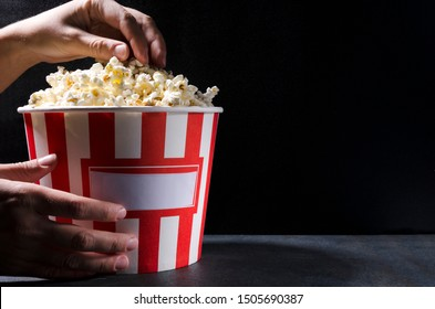 Woman in the cinema eating popcorn.A large bucket of salty popcorn against black wall.Empty space fo text