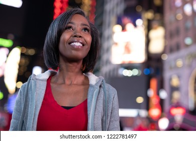 Woman in city at night feeling happy smile face