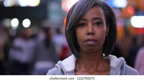 Woman in city at night serious