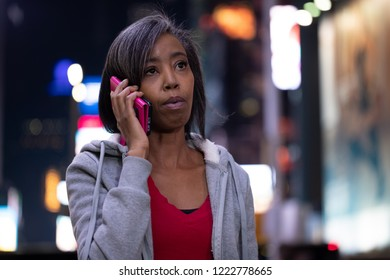 Woman in city at night talking on cell phone
