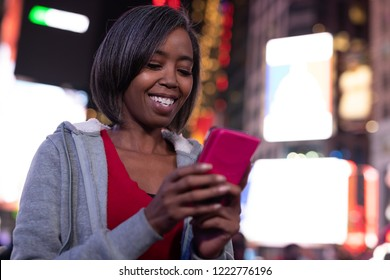 Woman in city at night using cell phone