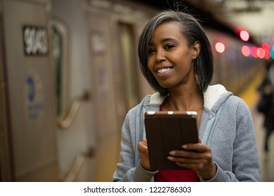 Woman in city at night using tablet computer