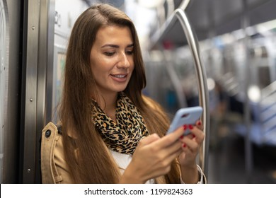 Woman in city on subway train using cell pohne
