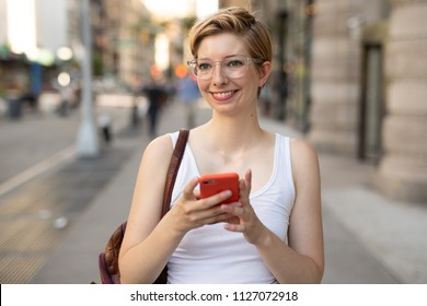 Woman in city walking texting cell phone