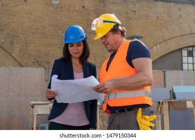 Woman civil engineer discussing about plans, blueprints and paperworks with the foreman on construction site