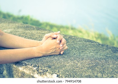 Woman claps or praying on rock table.