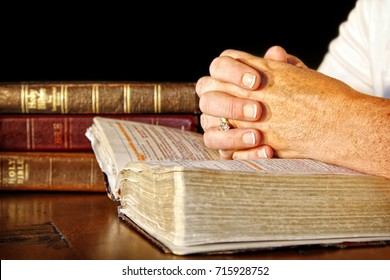 A woman clasps her hands in prayer on an open Holy Bible, while other bibles are stacked nearby on the table.