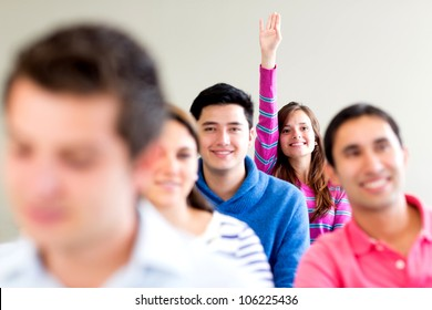 Woman in class raising her hand to participate