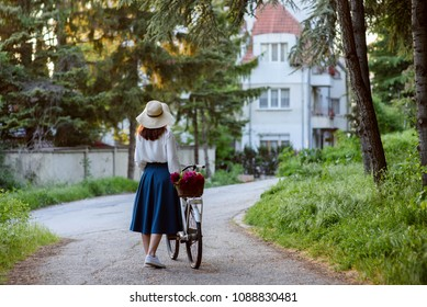 Woman with a classical bike walking in a park