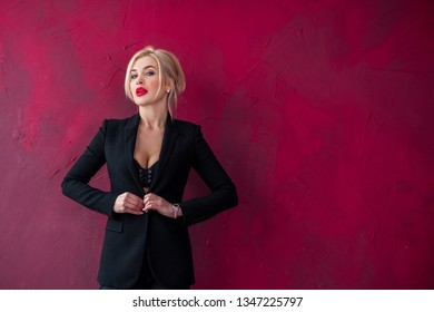 Woman in classical sexy black pantsuit , posing on red background. Concept of fashionable clothes