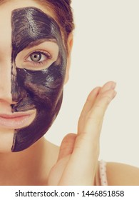 Woman with clay carbo detox black mask on her face. Girl taking care of oily skin complexion. Beauty treatment. Skincare.