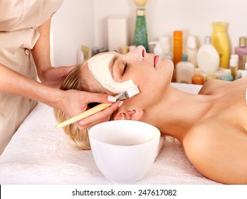 Woman with clay facial mask in beauty spa, are only visible hands causing mask to face