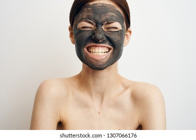 woman in clay mask with closed eyes shows teeth