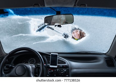 woman clean car of snow view from inside