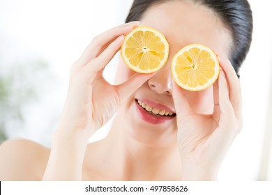 Woman with clean face holding slices of lemon over eyes. Lemon for beauty and health concept. indoors background