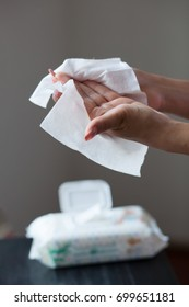 Woman clean hands with wet wipes, blurred package in background