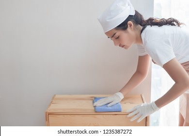 woman cleaner cleaning living room in apartment. portrait of asian woman cleaning staff doing housekeeping or domestic helper job. young adult asian woman model