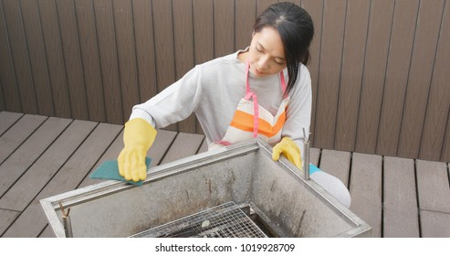Woman cleaning barbecue oven