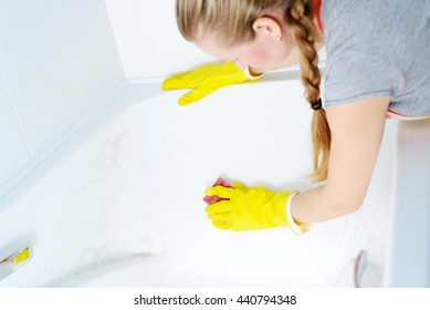 A woman cleaning bath at home. Female washing bathtub in yellow