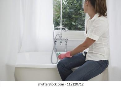 Woman cleaning bath tub