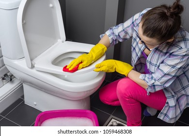 Woman is cleaning in the bathroom. Wash the toilet