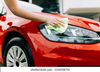 Woman cleaning car with microfiber cloth, car detailing (or valeting) concept.