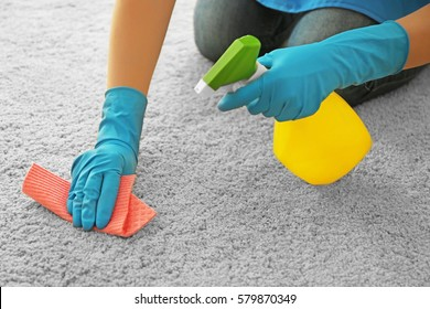 Woman cleaning carpet with detergent and napkin, closeup