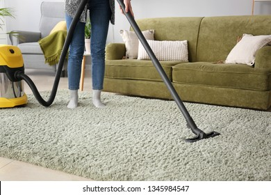 Woman cleaning carpet with hoover at home