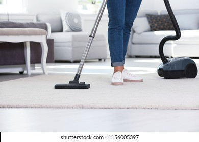 Woman cleaning carpet with vacuum cleaner, closeup