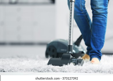 Woman cleaning the carpet with vacuum cleaner in the living room