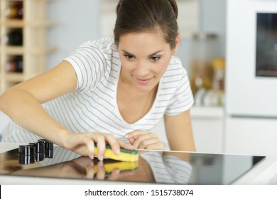 woman cleaning ceramic hob in the home
